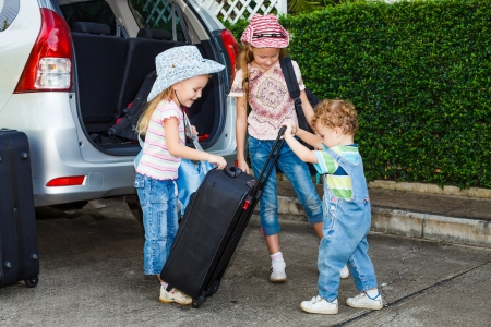 travel luggage: two little girls  and boy standing near the car with backpacks Stock Photo