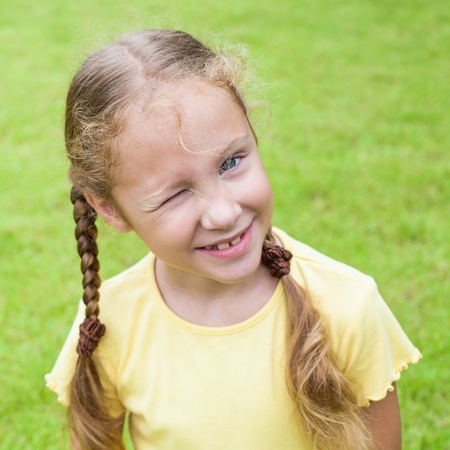 Portrait of happy child.  girl winking with one eye Stock Photo - 16890930