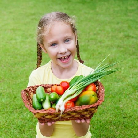 girl holding a basket of vegetables (cucumber, pepper, tomato, onion) photo