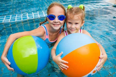 two little girls playing in the pool with balls  photo