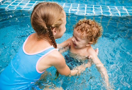 girl and little boy playing in the pool photo
