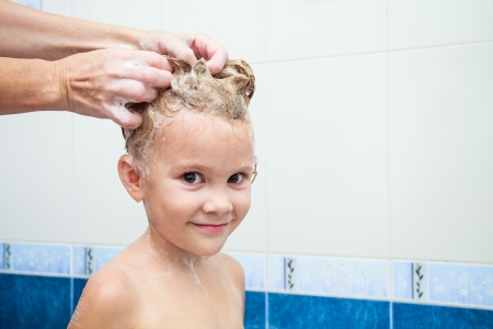 washing hair: Cute four year old girl taking a relaxing bath with foam Stock Photo