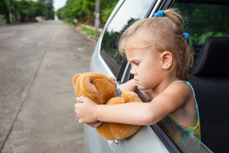 sad little girl sitting near the window in the car with toy in her hands photo