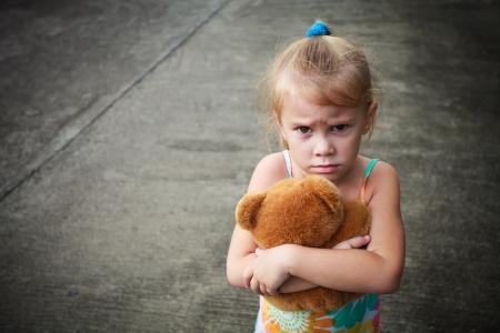petite fille triste: triste petite fille tenant jouet avec ses mains Banque d'images