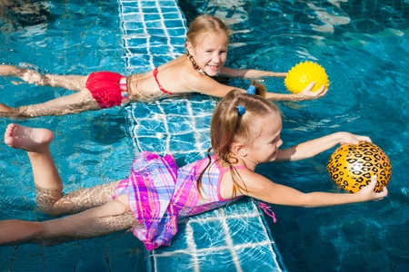 two little girls holding balls in their hands and playing in the pool Stock Photo - 16930952