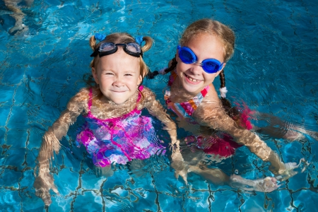 two little girls  playing in the pool photo