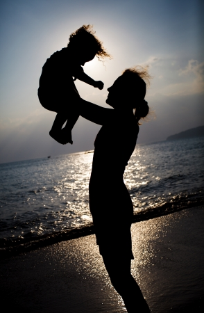 wean: Mother and little son silhouettes on beach at sunset