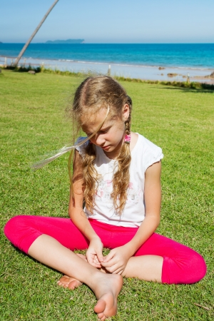 sad girl sitting on the grass near the sea photo