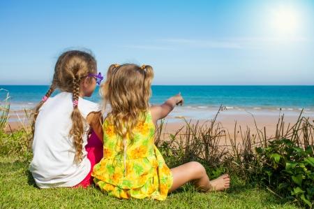 Twee meisjes zitten op het strand en kijken naar de zee Stockfoto