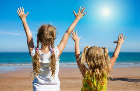 hands high: two girls near a sea pulling his hands to heaven