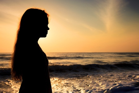 verdrietig meisje: Silhouet van een droevig kind op het strand
