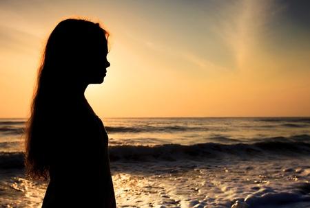 mujer pensativa: Silueta de un niño triste en la playa