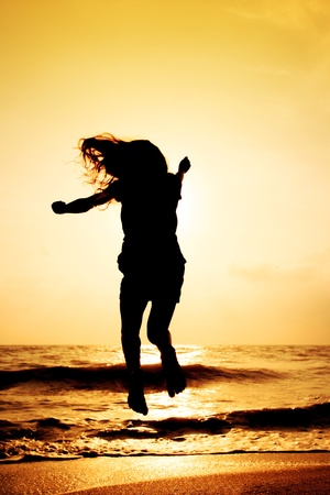 Happy girl jumping on the beach in sunset time photo