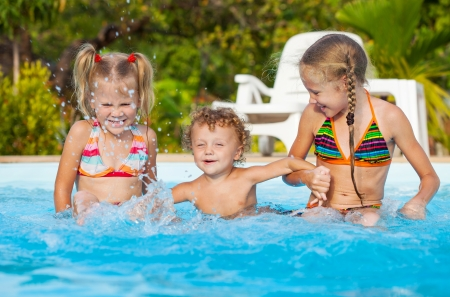 two little girls and little boy playing in the pool photo