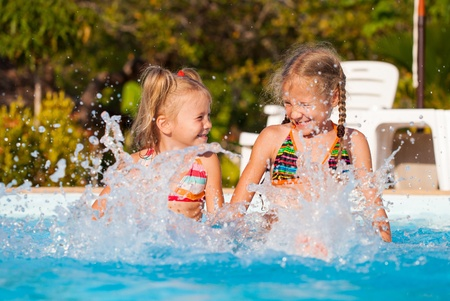 two happy little girls splashing around in the pool photo
