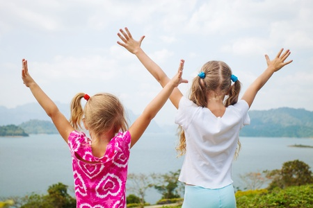 back up: two girls near a lake pulling his hands to heaven
