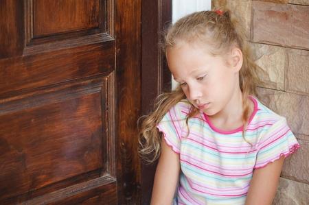 petite fille triste: triste petite fille assise près d'une porte sur le fond d'un mur de briques