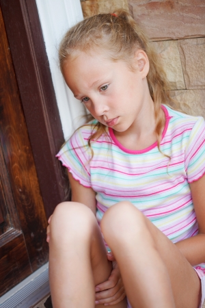 sad little girl sitting near a door on the background of an brick wall photo