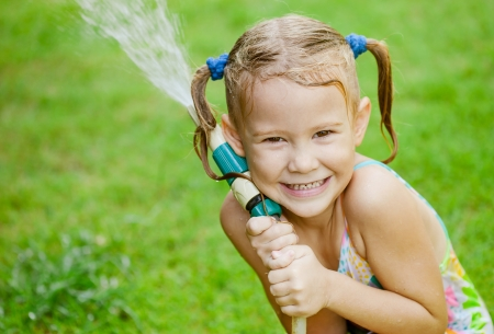 Happy girl pours water from a hose photo