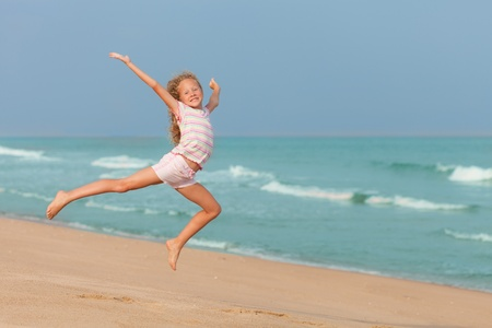 playing in the sea: flying jump beach girl on blue sea shore in summer vacation
