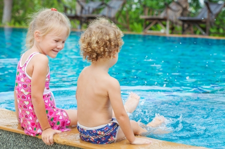 little girl and little boy sitting  in the swimming  pool photo