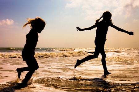 two kids silhouettes running on beach at sunset photo