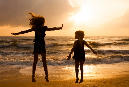 Happy girls jumping on the beach on the dawn time photo