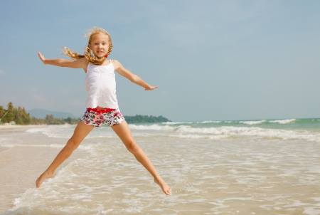 flying jump beach girl on blue sea shore in summer vacation photo