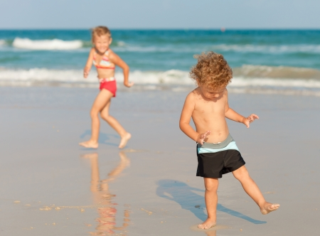 two happy kids playing on beach photo