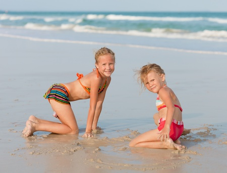 children sandcastle: Happy kids playing at the beach