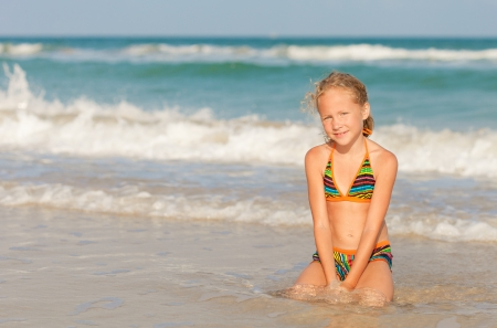 Adorable happy smiling girl on beach vacation photo