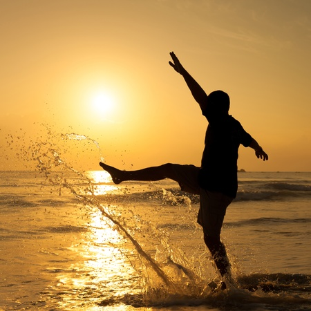 Happy man jumping over sea. Sand beach at dawn. photo