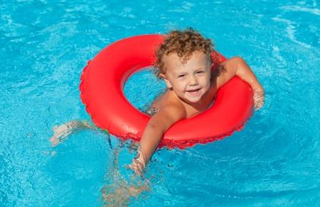 splash pool: ni�o en la piscina con el anillo de goma Foto de archivo