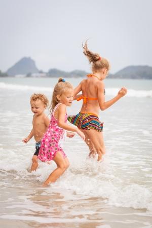 hermanos jugando: niños felices jugando en la playa