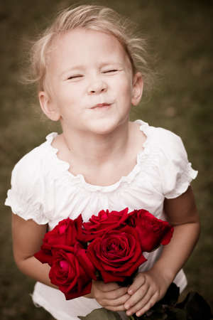 happy child with a bouquet of red roses photo
