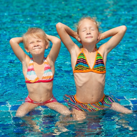 two happy little girls relaxing in the pool photo