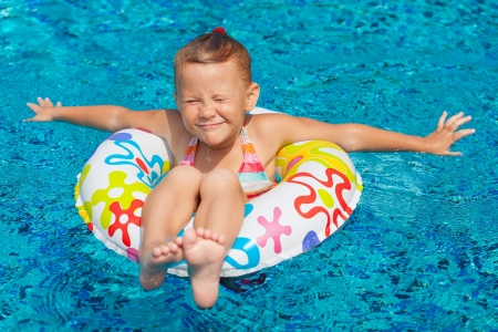 little girl in the swimming pool  with rubber ring photo