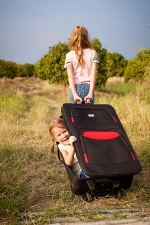 two little girls with suitcase on the road photo