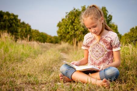 glädje: liten flicka sitter och läser en bok om naturen Stockfoto