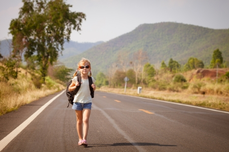 little girl with backpack walking on the road photo