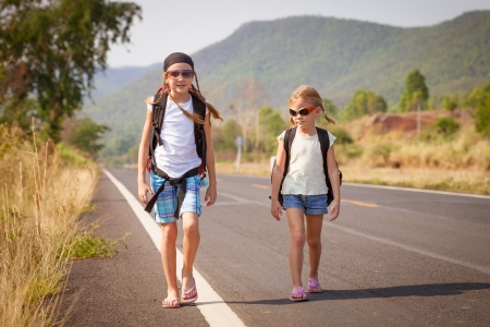 two little girls with backpack walking on the road photo