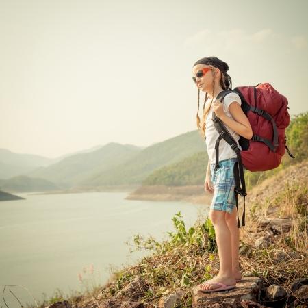 holčička s batohem odpoledne na břehu jezera photo