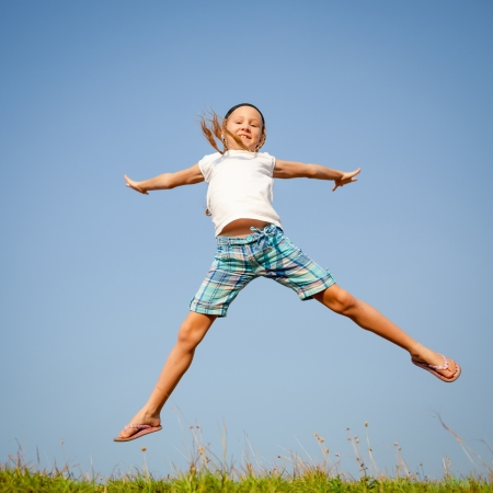 little girl jumping over the grass photo