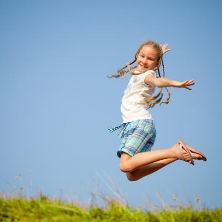 pulando: pouco menina pulando sobre a grama