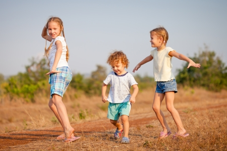 two little girls and little boy dancing on the road