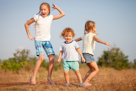 two little girls and little boy dancing on the road photo