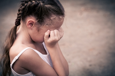 child sad: one sad child sitting on the floor and holding her head in her hands