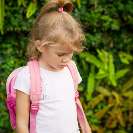 A young little girl preparing to walk to school photo