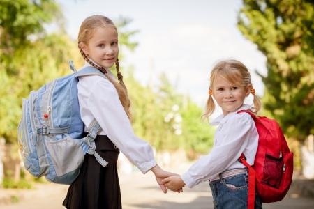 personas de espalda: dos jóvenes niñas se preparan para caminar a la escuela