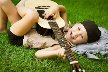 little girl playing on a guitar photo